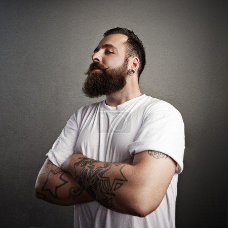 Tattooed brutal man wearing  t-shirt