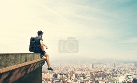 Photo for Young man is sitting on a roof and looking city - Royalty Free Image