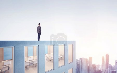 Businessman on a roof and looking at city
