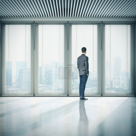 Businessman  in office and looking at megalopolis