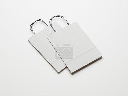 Foto de Folded paper bag with handles on paper background - Imagen libre de derechos