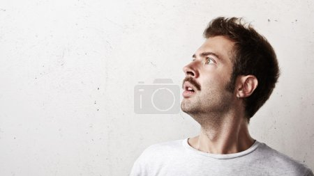 Portrait of a surprised young man with mustache...