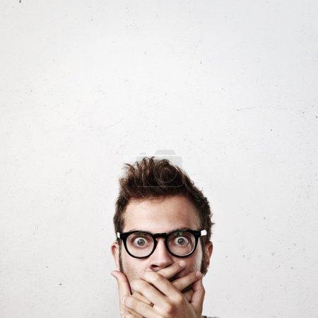 Surprised young man wearing eyeglasses
