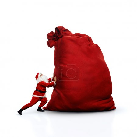 Photo for Santa Claus pushing huge red sack full of gifts - Royalty Free Image