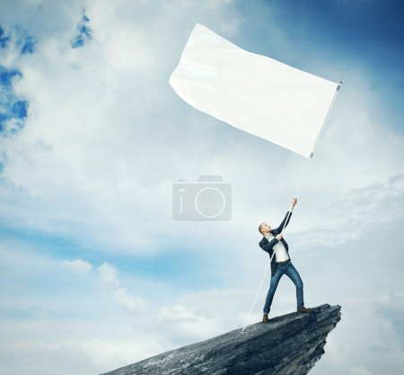 Man with white flag standing on a rock