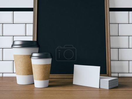 Photo pour Affiche noir sur la table avec les tasses à café blanc blanc, cartes de visite - image libre de droit