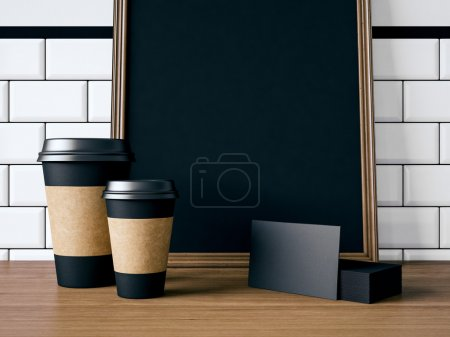 Photo pour Affiche noir sur la table avec les tasses à café blanc, cartes de visite - image libre de droit