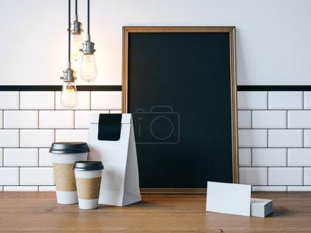 Photo pour Affiche noir sur la table avec les tasses de café vide, cartes de visite et lampes vintage - image libre de droit
