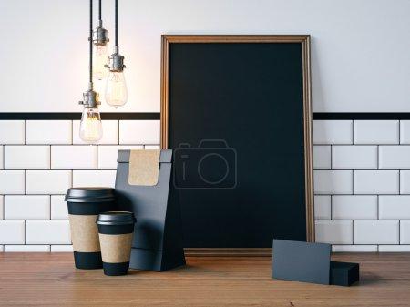 Photo pour Affiche noir sur la table avec les tasses de café vide, cartes de visite, des lampes vintage - image libre de droit