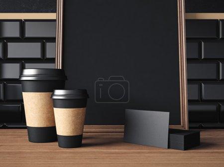 Photo pour Affiche noir sur la table avec les tasses de café vide, les cartes de visite, les caméra et les lunettes - image libre de droit