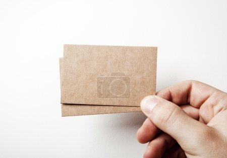 Photo pour Maquette de deux cartes de visite kraft vierges tenant dans une main mans sur le fond blanc - image libre de droit