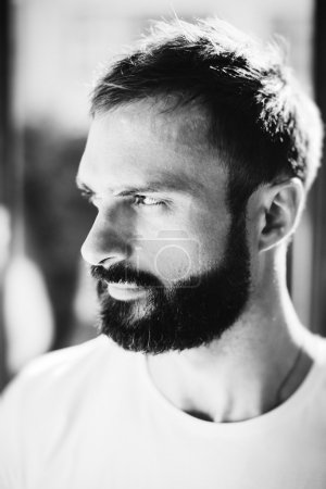 BW picture of a bearded man wearing white tshirt on the blure background