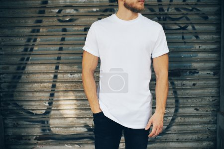 Photo for Portrait of a bearded man wearing blank t-shirt, blue jeans and standing on the street next to the garage - Royalty Free Image