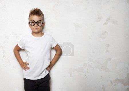 Photo pour Mignon petit garçon avec des lunettes souriant sur le fond du mur blanc - image libre de droit