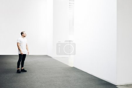 Young hipster walking in the white gallery