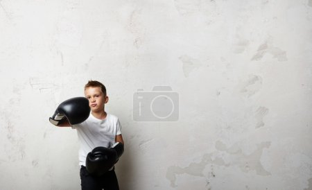 Photo for Little boxer standing in boxing gloves on the concrete wall background and shows his jab - Royalty Free Image