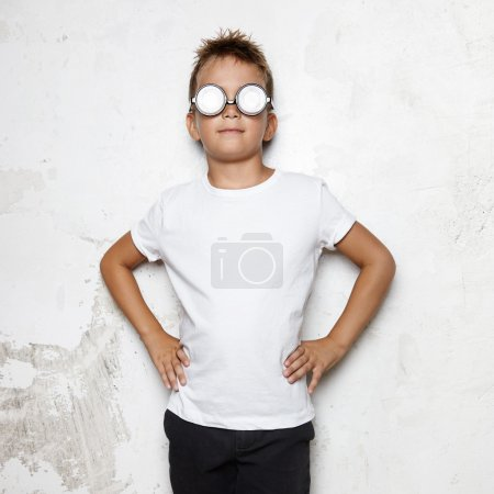 Boy in glasses stands on a wall background