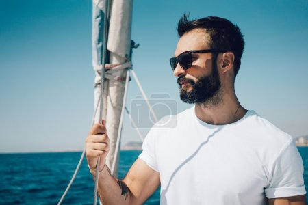 bearded man standing on a yacht