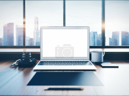 Generic laptop on the workspace with panoramic windows.  City at sunrise in a background. 3D rendering
