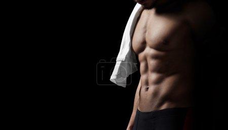Athletic man on black background. Closeup. Horizontal
