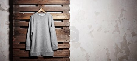 Photo for Photo of grey hoody  hanging in front of wood background. - Royalty Free Image