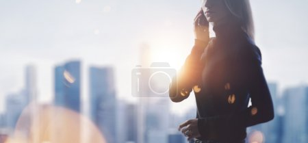 Portrait of young woman holding her smartphone in a hands. Blurred city on the background. Wide