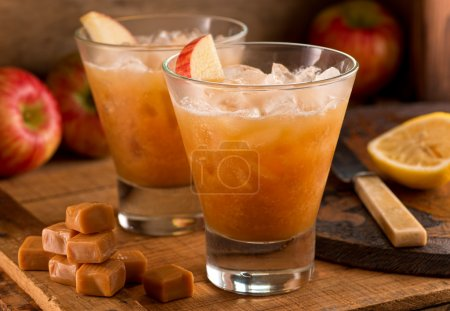 Photo pour Caramel Cocktails de cidre de pomme sur un fond rustique avec pommes, caramel et citron. - image libre de droit