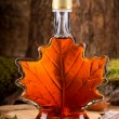 A bottle of delicious maple syrup in hardwood fore...