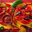 A group of bright colorful hot peppers on a red ba...