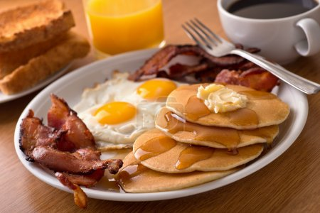 Photo for A delicous home style breakfast with crispy bacon, eggs, pancakes, toast, coffee, and orange juice. - Royalty Free Image