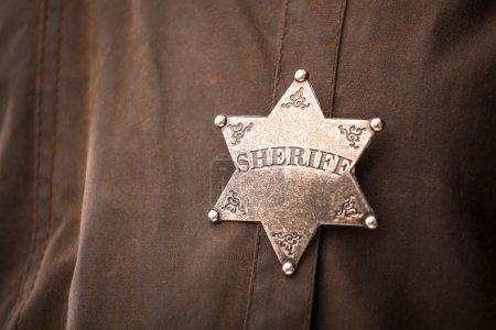 Photo pour Gros plan d'insigne de shérif quand le son plumeau de manteau - image libre de droit