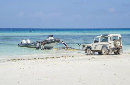 Photo pour Zanzibar, Tanzanie - 4 décembre 2014 : Hommes décevrons pas un jet-bateau de plongée dans l'eau sur la côte de Zanzibar. Bateau à moteur, Land Rover Defender et bateau traditionnel. - image libre de droit