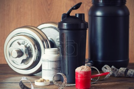 Whey protein powder in scoop with vitamins on plate on wooden background