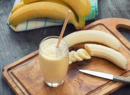 Foto de Batido de plátano hecho fresco sobre fondo de madera - Imagen libre de derechos