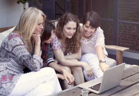 Happy group of female friends shopping on line