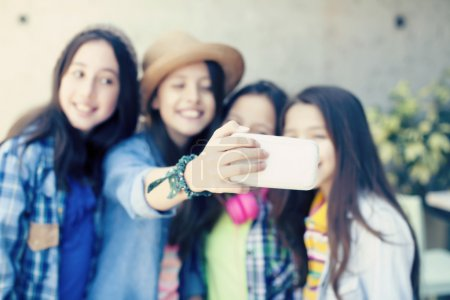 Outdoor portrait of friends taking photos with a smartphone