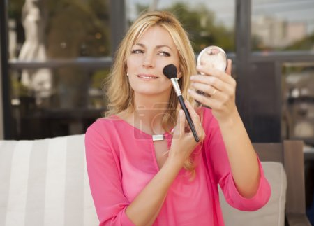 woman putting on makeup shot in outdoors