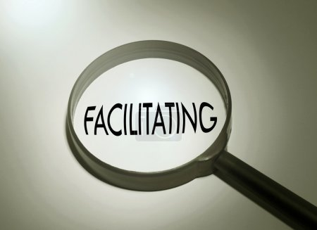 Magnifying glass with the word facilitating...