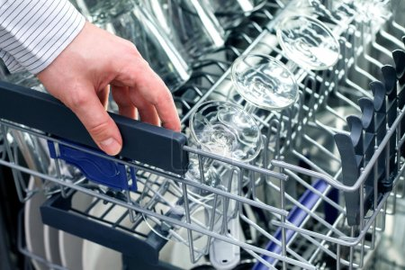 Man's hand opening dishwasher with clean utensils...