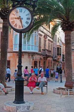 Menorca, Balearic Islands: a couple on a bench in the town square of Placa d'Alfons III, Ciutadella