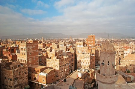 The Old City of Sana'a, decorated houses, palace, minarets and the mosque in the fog, Yemen