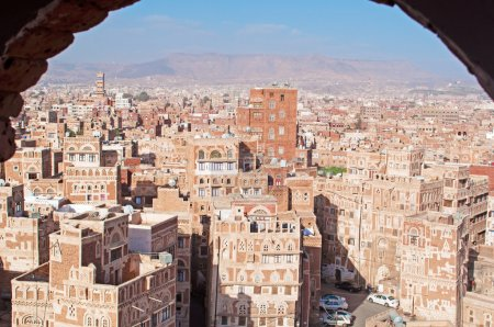 The Old City of Sana'a, decorated houses and palaces behind a stone arch, Yemen