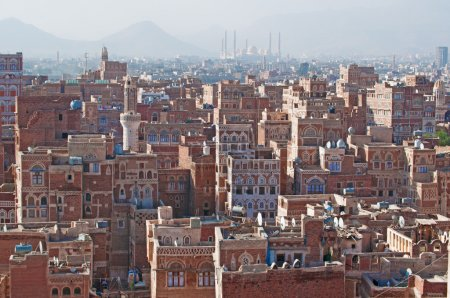 The Old City of Sana'a, decorated houses, palace, minarets and the Saleh Mosque in the fog, Yemen