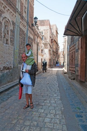 A yemeni man with a child on his shoulders walking in the streets of the Old City of Sana'a, Yemen, people, daily life