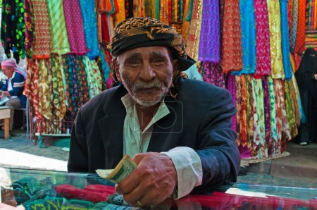 A yemeni old man pays after shopped at the fabric store in the salt market of the Old City of  Sana'a, Yemen, turban, scarves, foulard, daily life