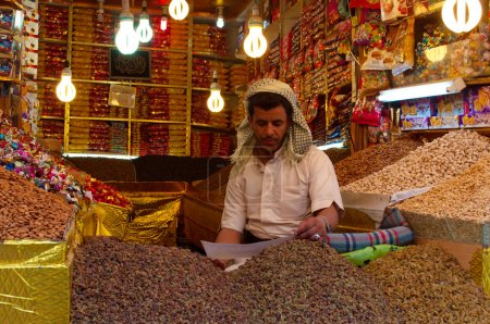 A yemeni man, seated in his shop in the salt market of the Old City of  Sana'a, suq, Yemen, seller, saffron, cereals, pulses, corn, nuts, daily life