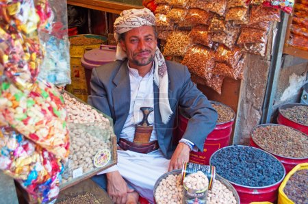 A yemeni man, seated at the entrance of his shop in the salt market of the Old City of  Sana'a, suq, Yemen, seller, candies, nuts and spices, daily life