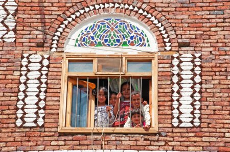 Five children, boys and girls, look out the window in a decorated house of the Old City of Sana'a, Yemen
