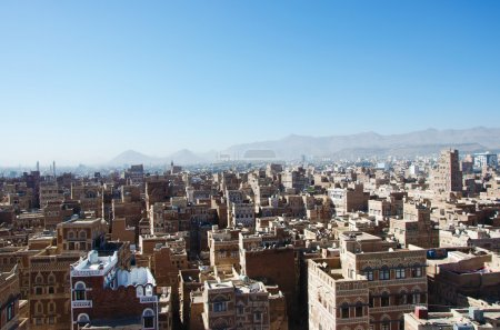The Old City of Sana'a, decorated houses, minarets and the Saleh Mosque in the fog, Yemen