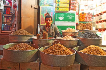 A yemeni boy, seated in his shop in the salt market of the Old City of  Sana'a, suq, Yemen, seller, spices and nuts, daily life